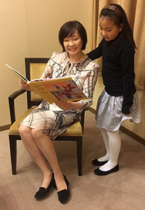 Japan First Lady Akie Abe enjoys reading the bilingual English/Japanese Jester with Junior Jester Sophia Muratsuchi.