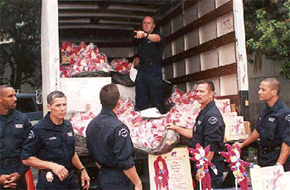 Police officers from L.A.P.D. unload Jester & Pharley books and dolls to lift the spirits of children in distress.
